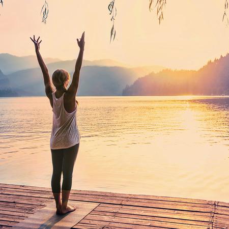 horizont: Beautiful woman practicing Yoga by the lake - Sun salutation series - Toned image Stock Photo