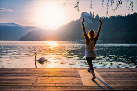 salute: Beautiful woman practicing Yoga by the lake - Sun salutation series - Swan passing by - Toned image