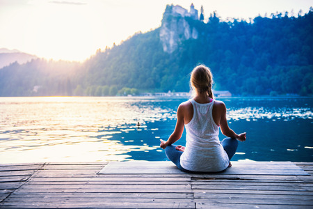 Young woman meditating by the lake Imagens - 57148610