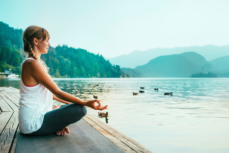 water birds: Beautiful woman in lotus position, meditating by the lake, sunset, water birds Stock Photo