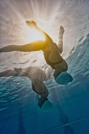 Synchroonzwemmen vrouwen duet - onderwater beeld van gesynchroniseerde zwemmers, afkomstig van onderen tegen de zon Stockfoto