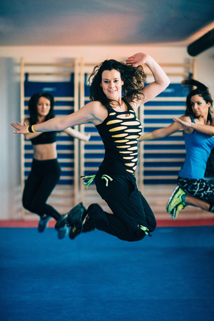 four person only: Young woman jumping at Zumba fitness class