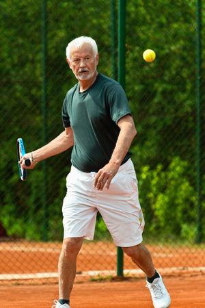 moving activity: Senior sportsman playing tennis