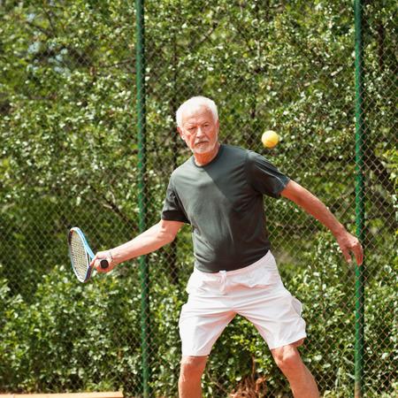 70s tennis: Senior man playing tennis