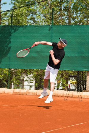 70s: Active senior man in his 70s playing tennis Stock Photo