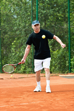 70s tennis: Active senior man playing tennis in his 70s Stock Photo