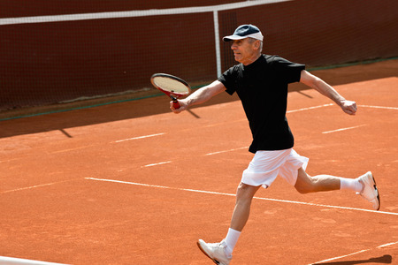 70s tennis: Active senior tennis player running for ball Stock Photo