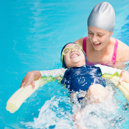 little boy swimming: Swimming lesson - little boy swimming on back with swimming noodle Stock Photo