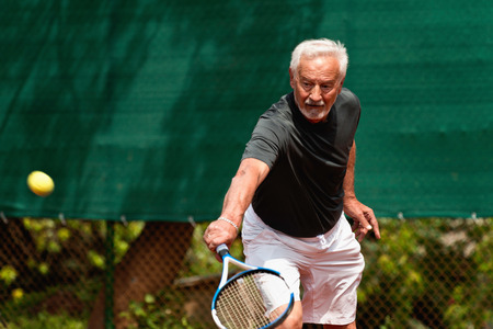 70s tennis: Senior man in action, playing tennis