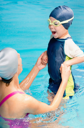 breath taking: Cheerful little boy taking breath on a swimming class