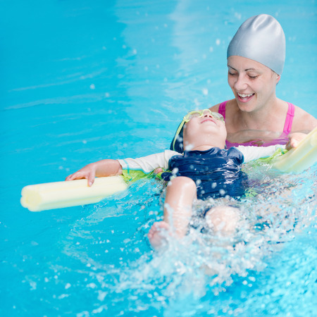 little boy swimming: Little boy swimming on back with swimming noodle Stock Photo