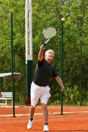 only one senior adult man: Senior tennis player serving Stock Photo
