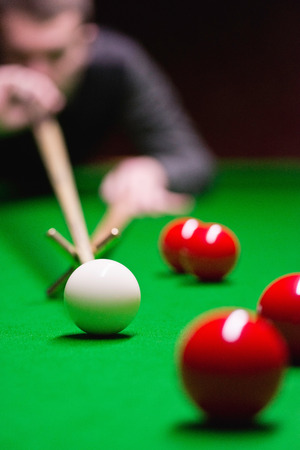snooker cue: Snooker - cue ball in focus, shot played with rest, professional player blurred in background