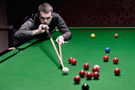 toned image: Professional snooker player taking shot. Low key, toned image