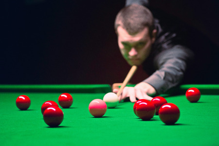 Snooker player going for pink. Ball in focus, face blurred in distance. Ambient light, slightly toned for atmosphere