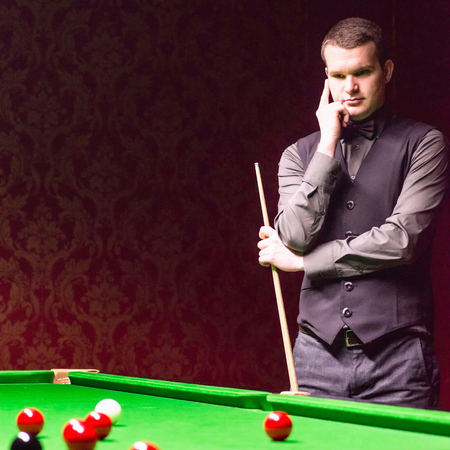 snooker hall: Professional snooker player, contemplating over table.