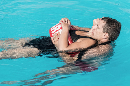flotation: Lifeguard rescue training - young man swimming with drowning victim, keeping her head above water surface