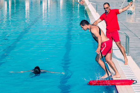 Lifeguard rescue training - young man swimming with drowning victim, keeping her head above water surface