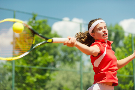 Action shot of young female tennis player hitting forehand