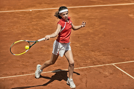 forehand: Young female tennis player approaching net during game, attacking with forehand Stock Photo