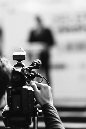 publicity: Tv camera recording spokesman at publicity event. Black and white Stock Photo
