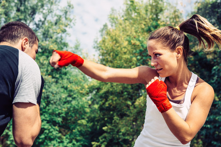 two persons only: Woman throwing a punch to man on taebo training Stock Photo