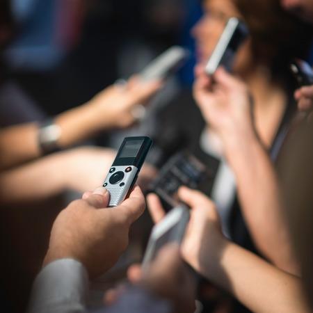 Journalisten Nachrichten zu machen, kämpfen, um Antworten zu erhalten. Fokus auf Voice-Recorder, verschwommenes Menge