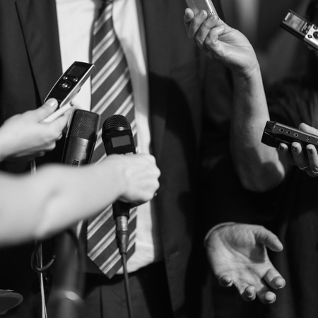answering: Politician answering media questions, defensive gesturing. Retro style, black and white processing Stock Photo