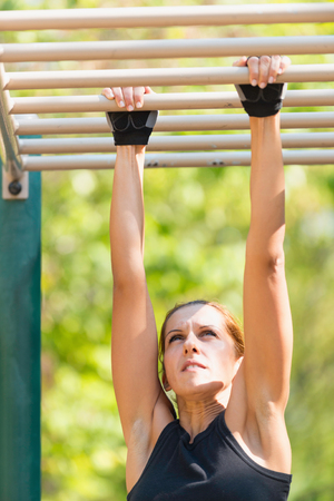 rung: Rung to rung exercise on monkey bar by female Stock Photo