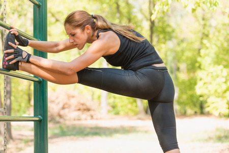 touching toes: Young female athlete stretching her legs