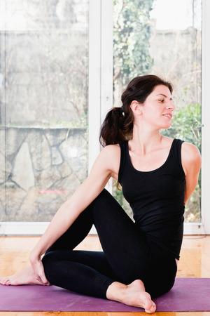 buena postura: Mujer que hace yoga en casa - giro espinal o Ardha Matsyendrasana. Ligeramente tonos imagen.