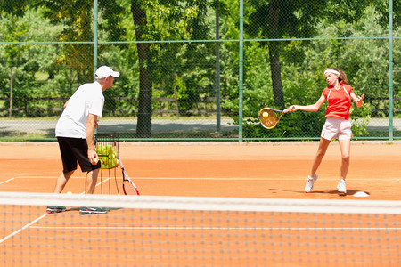 Tennis instructor working with student - practicing forehands