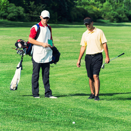 two persons only: Golfer and caddy on the golf course, ball lying in rough. Stock Photo