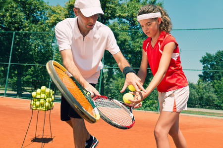 Tennis lesson - instructor working with teenager. Toned image Foto de archivo