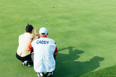 Golfer and caddy reading green 版權商用圖片