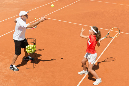 Junior tennis player in training with coach