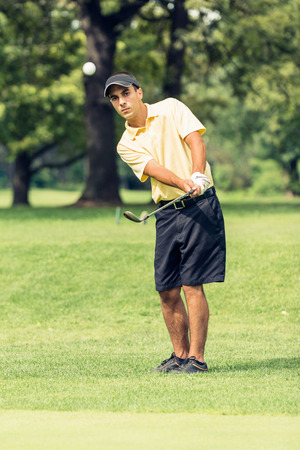 chipping: Golf Chipping - Golfer playing a chipping shot. Stock Photo