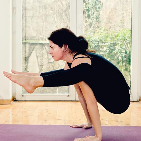 buena postura: Mujer que hace yoga en casa - Tittibhasana o Firefly Posici�n. imagen ligeramente entonada Foto de archivo