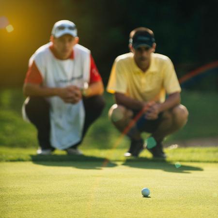 Golfeur et caddy lecture vert. Une balle de golf au point, l'image tonique