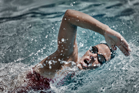 High speed swimming. Precise focus set on face, high speed desaturated film style, XXXL format, D800 Stock Photo