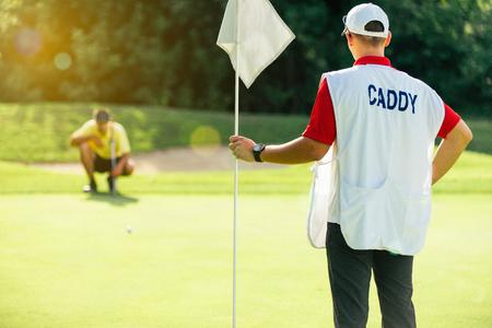 ゴルフ - ゴルファー読書緑のフラグを保持しているキャディー 写真素材