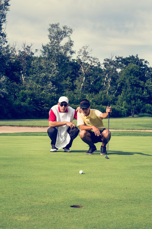 two persons only: Golfer and caddy, contemplating putting shot. Toned image Stock Photo