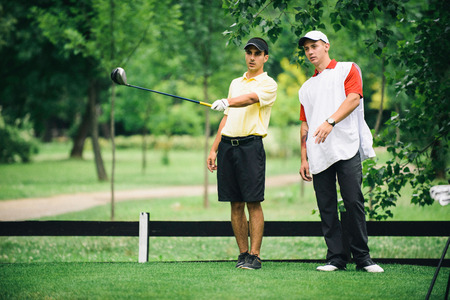 estimating: Golfer and caddy talking on the tee box. Toned image Stock Photo