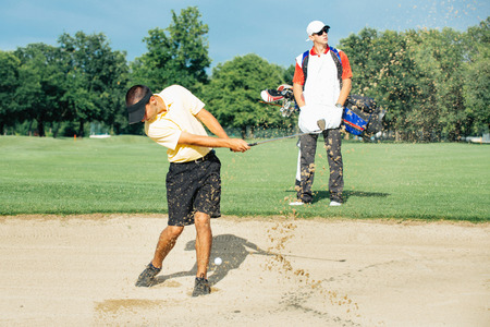 action shot: Golfer playing from sand bunker, action shot Stock Photo
