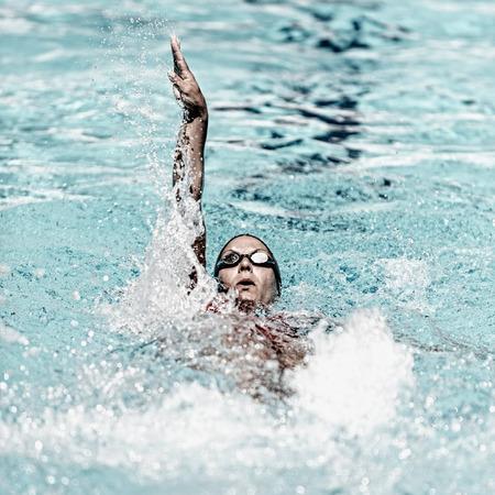 backstroke: Backstroke swimming moment. Precise focus set on face, high speed