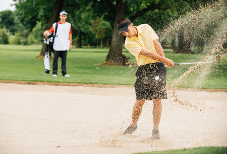 action shot: Action shot of golfer playing from sand trap, caddy behind Stock Photo