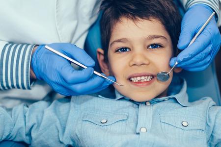 dental health: Dentist doing regular dental check-up to little boy. Stock Photo