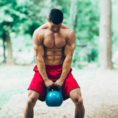kettle bell: Muscular crossfit athlete exercising outdoors with kettle bell Stock Photo