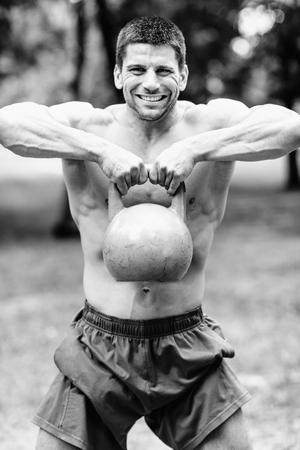 kettle bell: Crossfit athlete exercising with kettle bell. Black and white Stock Photo