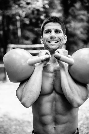 kettle bell: Crossfit athlete training with two kettle bell weights. Black and white